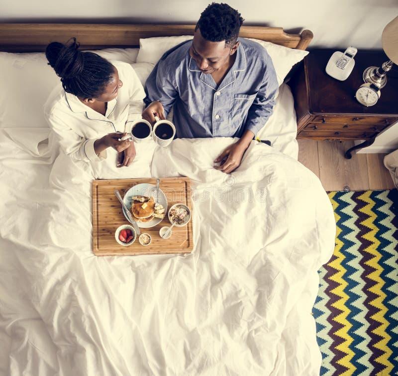 Amerykanin Afrykańskiego Pochodzenia para w łóżku ma śniadanie w łóżku fotografia stock