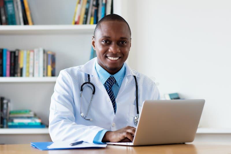 Amerykanin afrykańskiego pochodzenia szefa kuchni lekarz pracuje przy komputerem fotografia stock