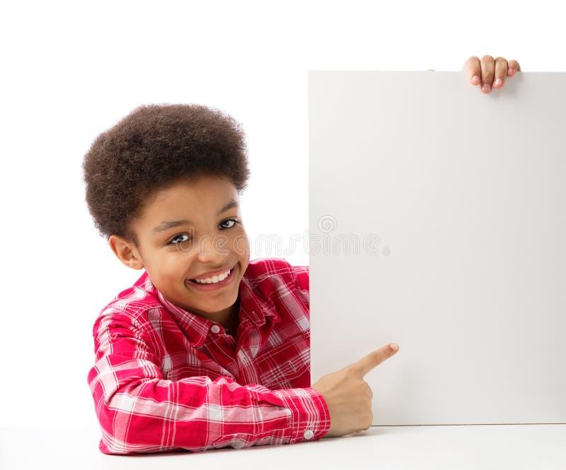 Amerykanin Afrykańskiego Pochodzenia szkolna chłopiec wskazuje przy białym pustym miejscem zdjęcia stock