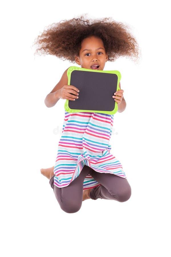 Amerykanin Afrykańskiego Pochodzenia szkolna dziewczyna trzyma pustą czerni deskę - czerń fotografia royalty free