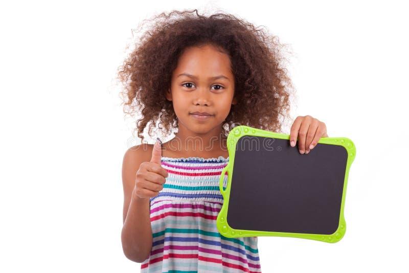 Amerykanin Afrykańskiego Pochodzenia szkolna dziewczyna trzyma pustą czerni deskę - czerń zdjęcia stock