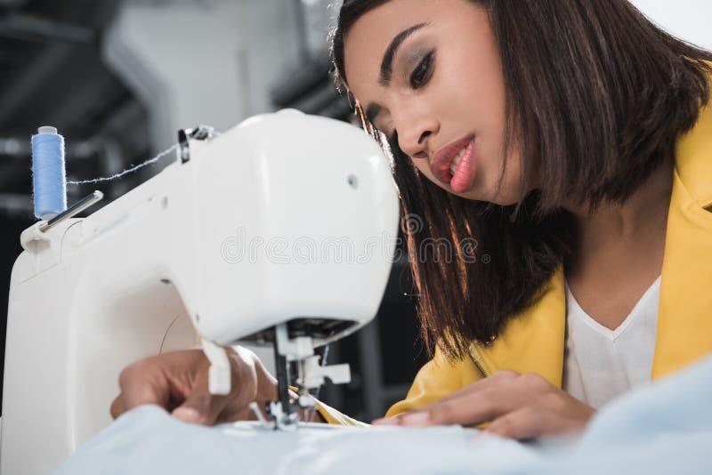 Amerykanin afrykańskiego pochodzenia szwaczka pracuje z szwalną maszyną obrazy royalty free