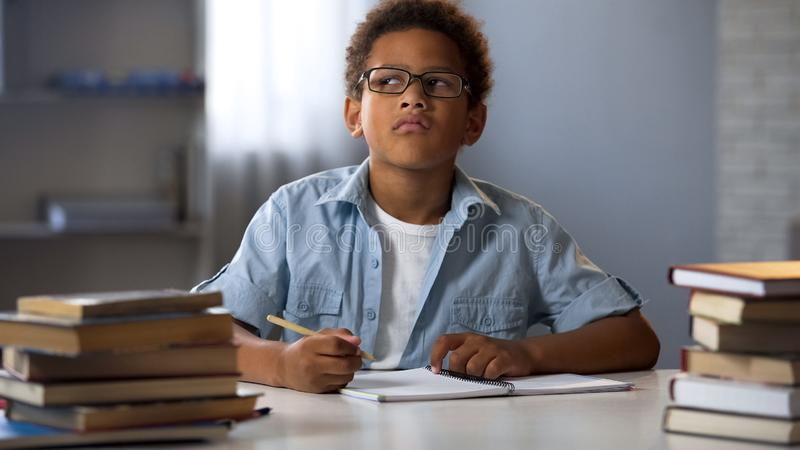 amerykanin chłopiec główkowanie na szkolnym eseju, mądrze dzieciak robi pracie domowej, edukacja obraz stock