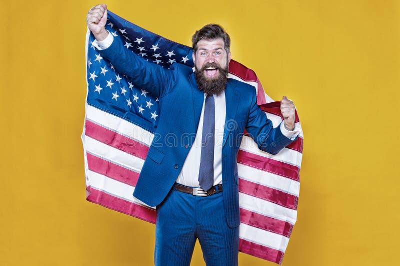 Amerykanin narodziny Buntownik wyborem Ufnego biznesmena przystojny brodaty mężczyzna w formalnym kostiumu chwyta flagi usa Bizne zdjęcie stock