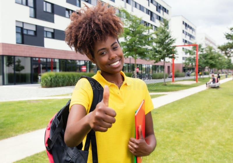 Amerykanina afrykańskiego pochodzenia żeński uczeń pokazuje kciuk plenerowego na kampusie fotografia royalty free