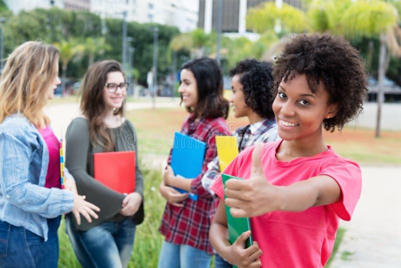 Amerykanina afrykańskiego pochodzenia żeński uczeń z grupą międzynarodowa stadnina obraz royalty free