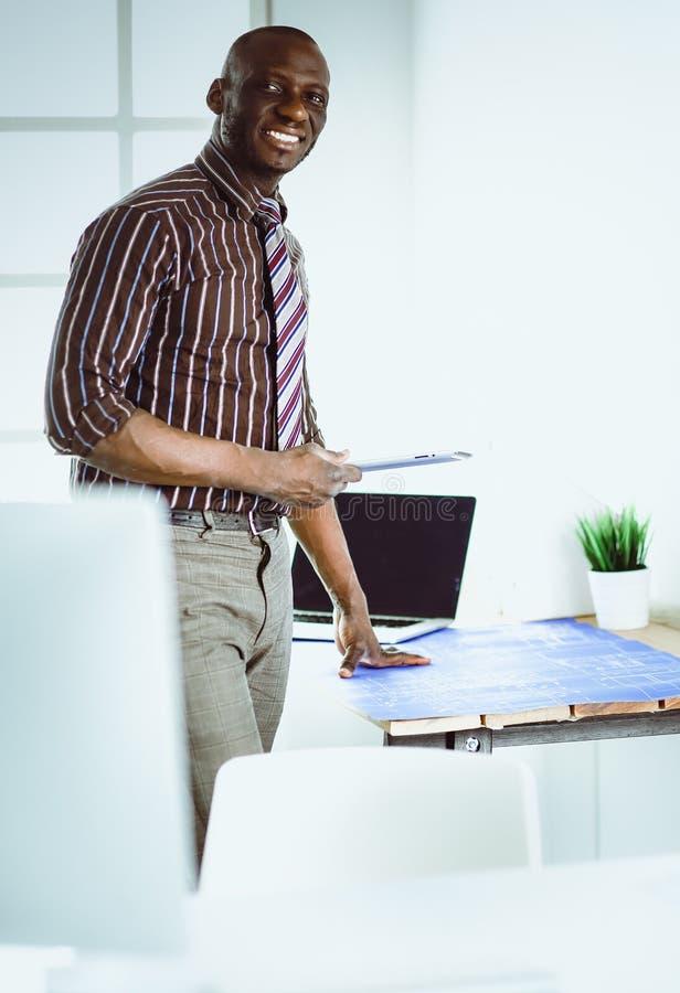 Amerykanina afrykańskiego pochodzenia architekt pracuje z komputerem i projektami w biurze obraz stock