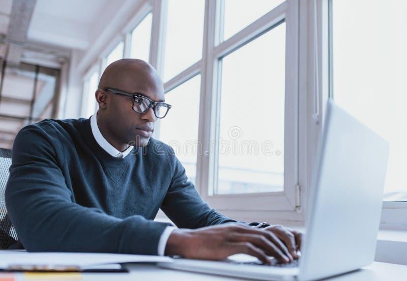 Amerykanina afrykańskiego pochodzenia biznesmen pracuje na jego laptopie fotografia stock