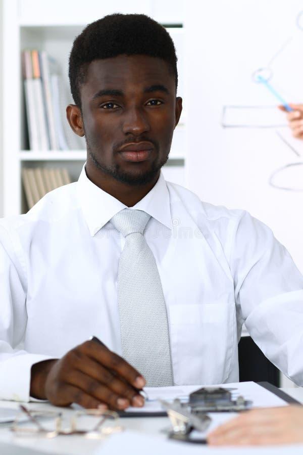 Amerykanina afrykańskiego pochodzenia biznesmen przy spotkaniem w biurze, barwiącym w bielu Wielo- etniczni ludzie biznesu grup fotografia stock
