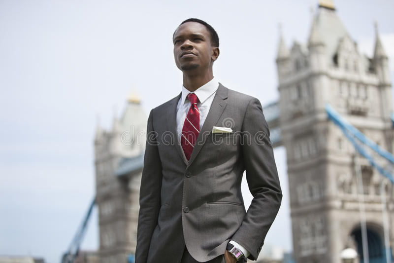 Amerykanina Afrykańskiego Pochodzenia biznesmena pozycja przeciw Londyn mostowi zdjęcie stock