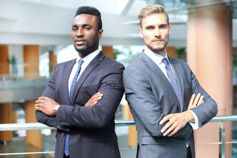 Amerykanina afrykańskiego pochodzenia i caucasian partnery biznesowi trwanie z powrotem popierać wpólnie i patrzejący w kamerze,  obraz stock