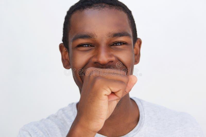 Amerykanina afrykańskiego pochodzenia mężczyzna śmia się z ręki nakrywkowym usta zdjęcia stock