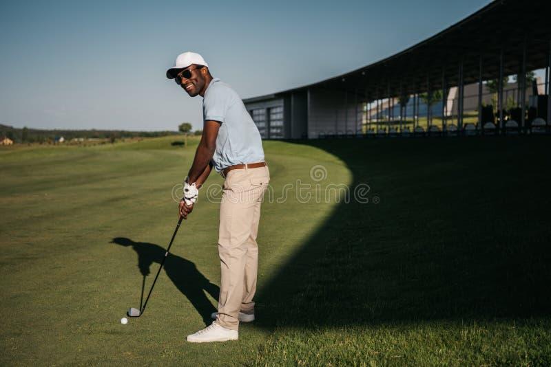 Amerykanina afrykańskiego pochodzenia mężczyzna bawić się golfa z klubem i piłką przy zielonym gazonem zdjęcia royalty free
