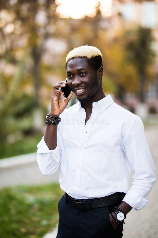 Amerykanina afrykańskiego pochodzenia mężczyzna opowiada telefonem komórkowym w pogodnej miasto ulicie obraz stock