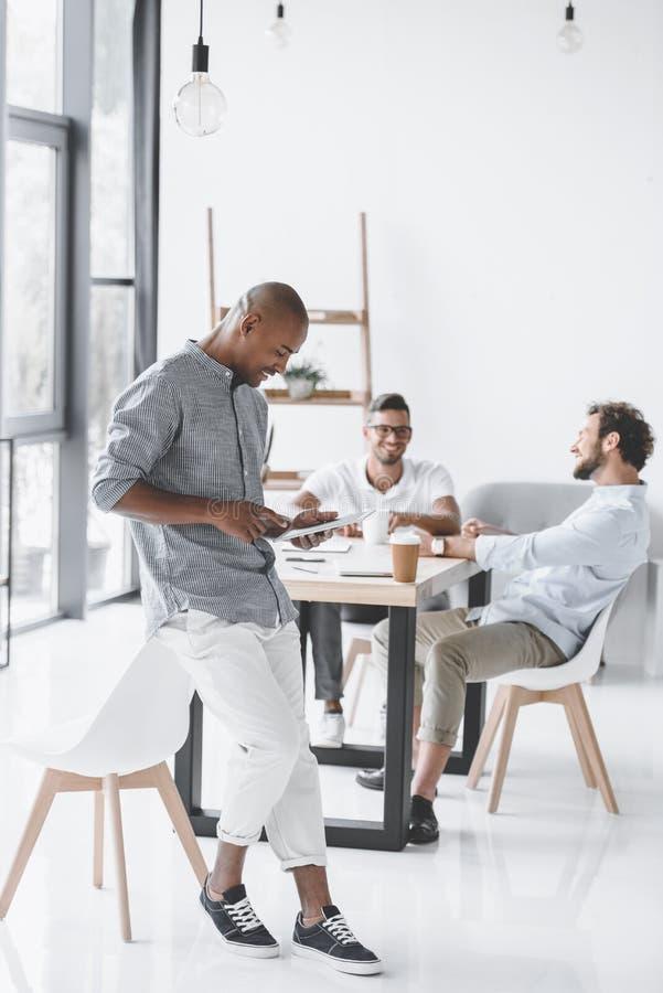 amerykanina afrykańskiego pochodzenia mężczyzna używa pastylkę przy miejscem pracy podczas gdy koledzy dyskutuje strategię fotografia stock