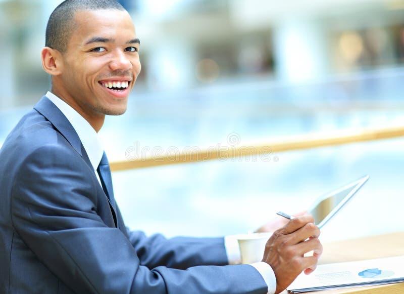 Amerykanina Afrykańskiego Pochodzenia mężczyzna z pastylka komputerem w nowożytnym biurze obraz royalty free