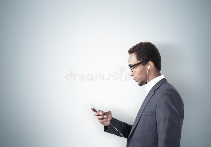 Amerykanina Afrykańskiego Pochodzenia mężczyzna z smartphone, szarości ściana obrazy stock