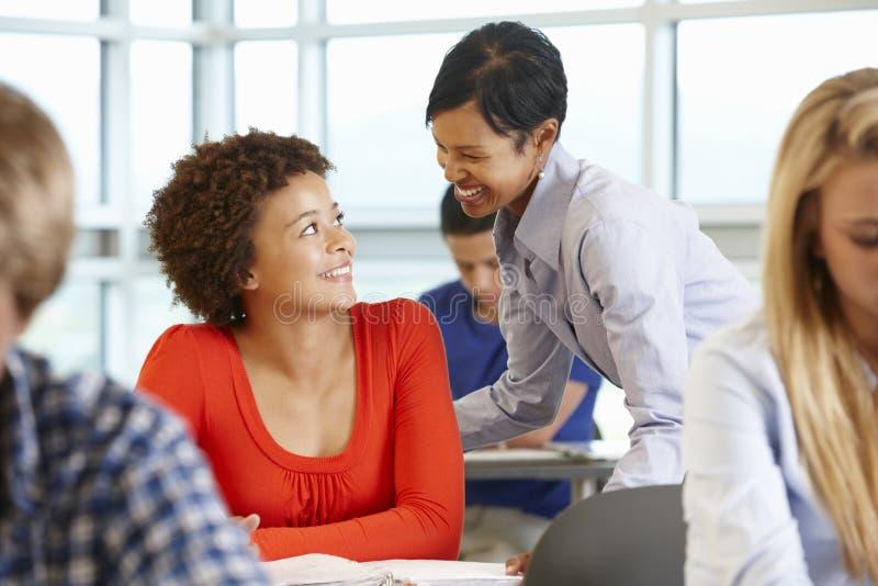 Amerykanina Afrykańskiego Pochodzenia nauczyciela pomaga uczeń w klasie zdjęcie royalty free