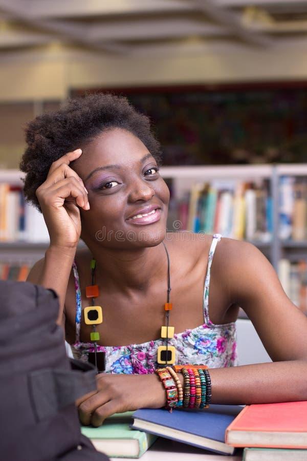 Amerykanina Afrykańskiego Pochodzenia uczeń przy Bibliotecznym studiowaniem zdjęcia stock