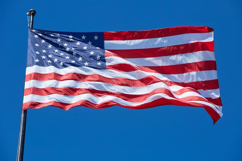 Amerykanina lub usa flaga w wiatrze na jasnym niebieskim niebie zdjęcie royalty free