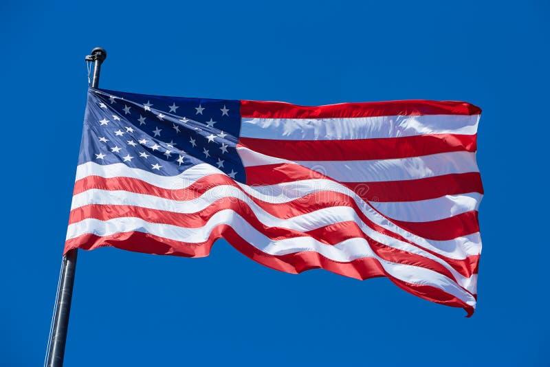 Amerykanina lub usa flaga w wiatrze z flagpole na niebieskim niebie zdjęcie royalty free
