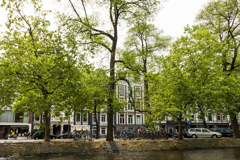 Amesterdam, Holland – 2019. Cars and bicycles parked near canal of river Amstel in narrow streets of Amsterdam city. Old dutch. Houses painted in bright royalty free stock photography