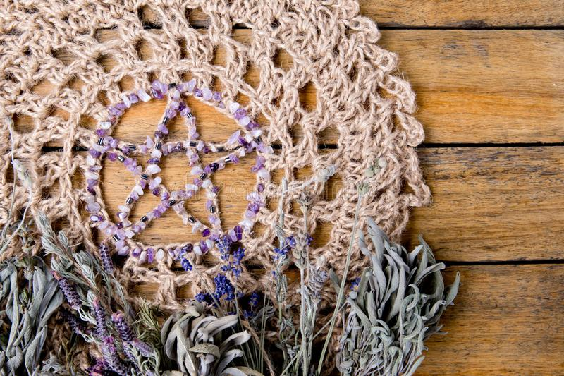 Amethyst Pentagram with dried herb bundles on crotchet jute altar cloth with rustic wooden background. Amethyst crystal Pentagram with dried herb bundles on stock photos