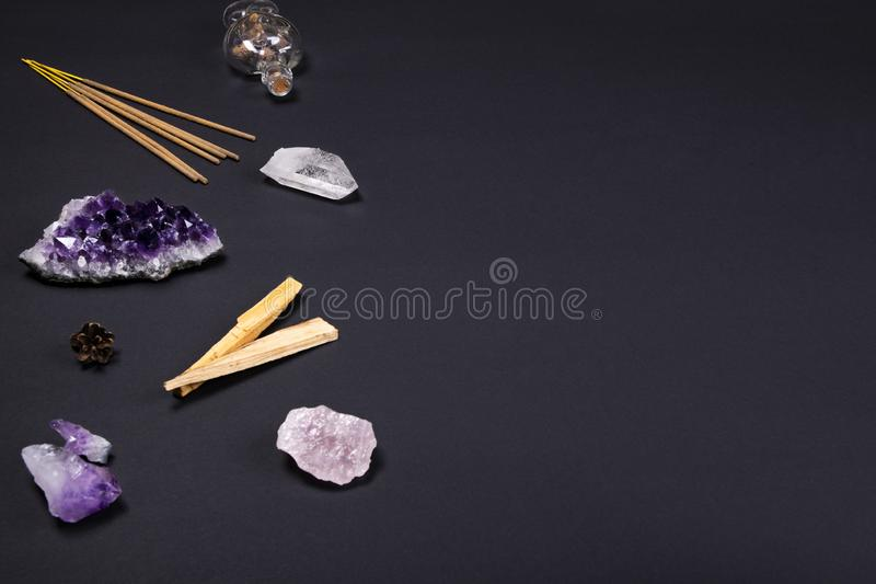Amethyst and quartz crystal stones, palo santo wood, aromatic sticks, cone and decorative bottle on black background stock images