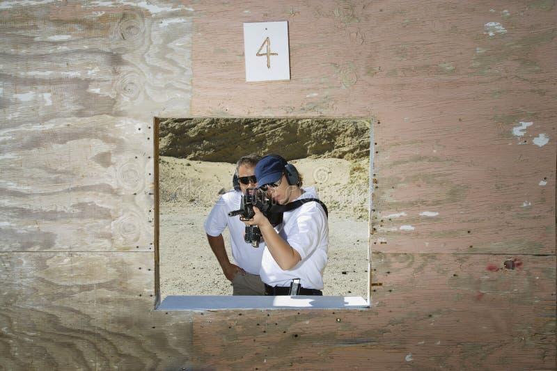 Ametralladora de With Woman Aiming del instructor en la gama de leña fotografía de archivo