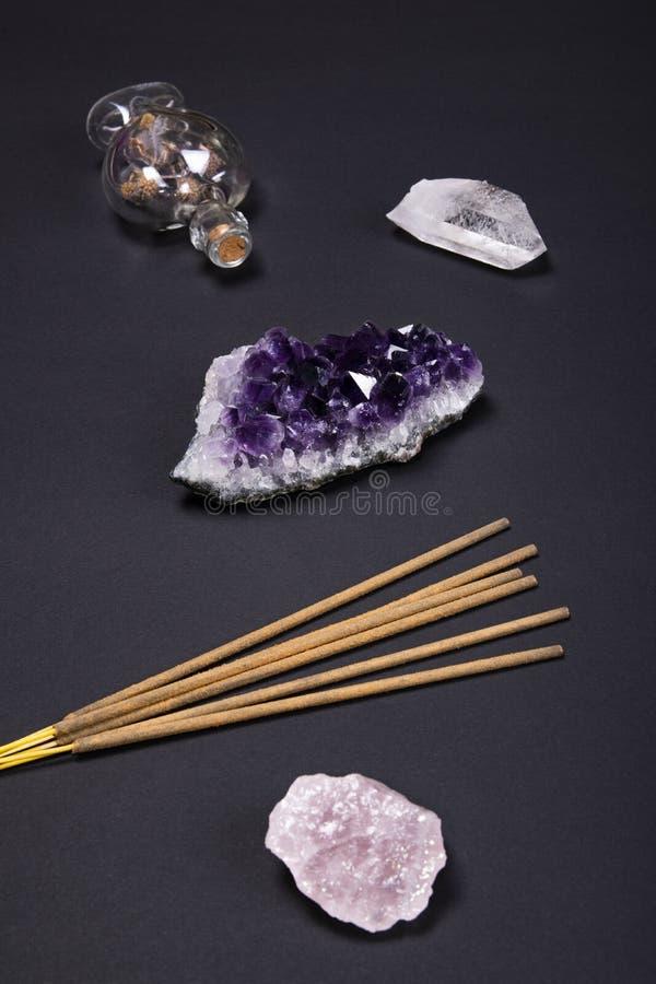 Ametystowego i kwarcowego kryształu kamienie aromatyczni kije i dekoracyjna butelka na czarnym tle, fotografia royalty free