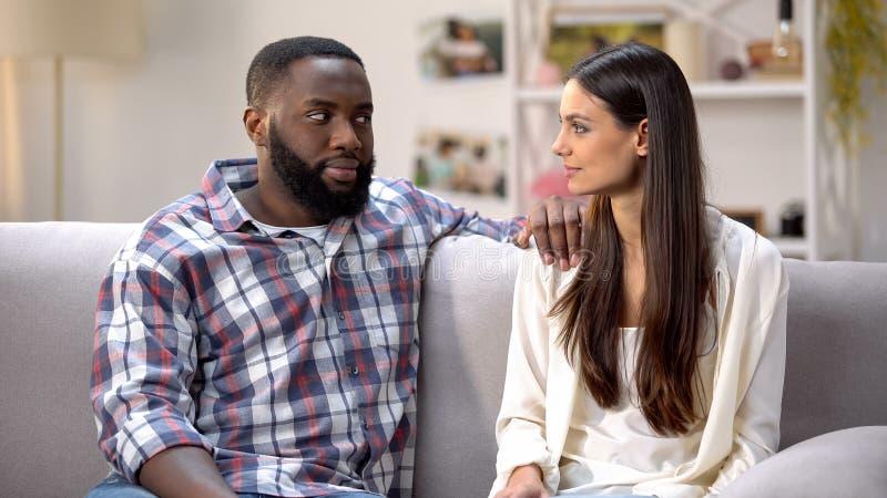 Ami afro-américain regardant soupçonneusement l'amie, surprise pour aimé photo stock