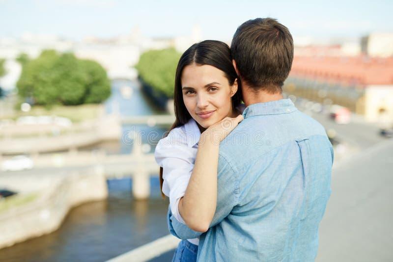 Ami de embrassement de fille attirante satisfaite sur le toit image stock