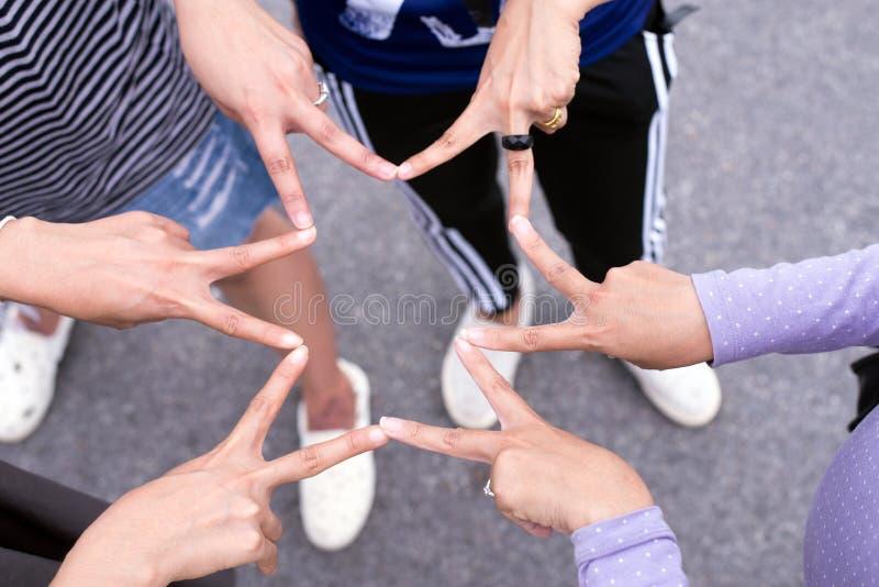 Ami de femmes mettant avec les mains et le signe d'étoile de posture de doigt et montrant ensemble, concept réussi de travail d'é image libre de droits