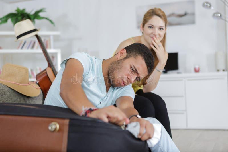 Ami essayant de fermer la valise de bagage ? la maison image libre de droits