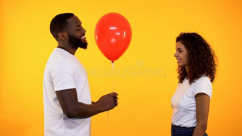 Ami heureux donnant le ballon rouge à l'amie sur le fond orange, date photos stock