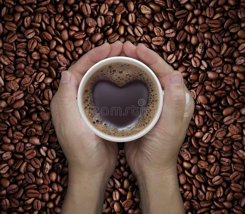 Ami la tazza di caffè in mani con forma del cuore sul fagiolo fotografie stock