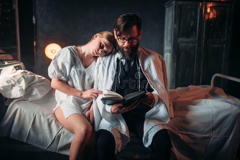 Ami le coppie che leggono un libro nella stanza di ospedale fotografia stock