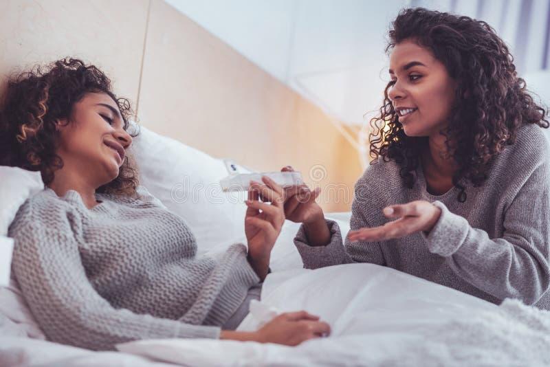 Ami soigneux rendant visite à son ami malade souffrant de la grippe à la maison images libres de droits