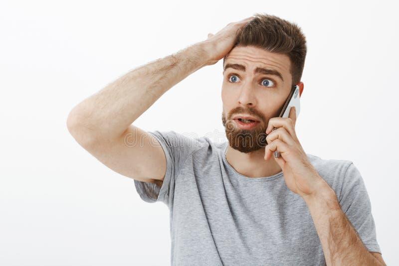 Ami soucieux intéressé et préoccupé recevant la mauvaise nouvelle pendant l'appel téléphonique tenant le bras sur le front regard photo stock