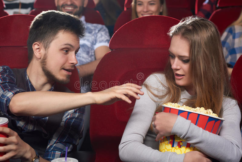 Ami tirant la main au maïs éclaté de son amie d'avidité images libres de droits