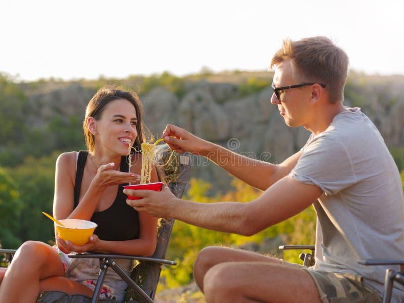 Amica e ragazzo che mangiano le tagliatelle su uno sfondo naturale Divertiresi turistico felice delle coppie Concetto economico d immagini stock