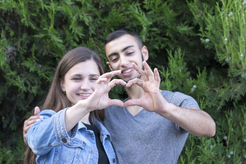 Amica e ragazzo che mostrano forma del cuore immagini stock