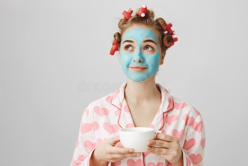 Amica europea sveglia vaga in capelli-bigodini ed in pigiami, stando nella maschera facciale blu, tenendo tazza di tè, sorridente fotografie stock