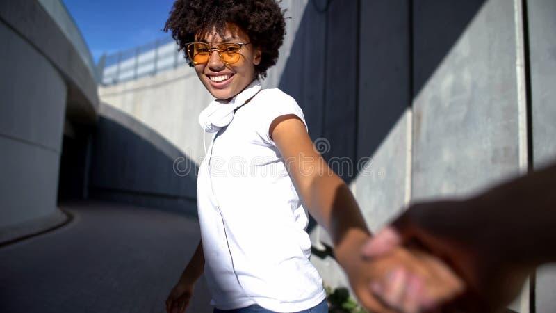 Amica seguente del tipo, tenente mano di signora sorridente, relazione felice della gioventù immagini stock