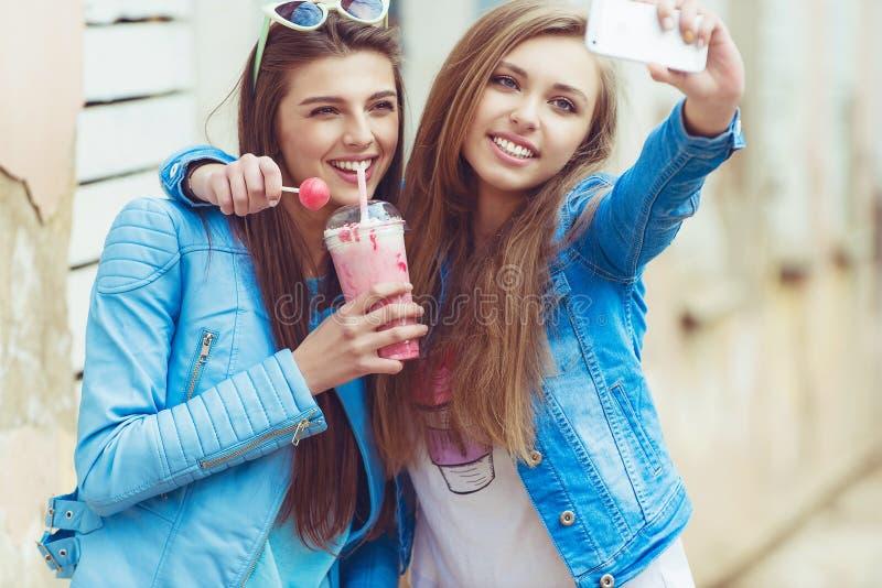 Amiche dei pantaloni a vita bassa che prendono un selfie in città urbana immagine stock