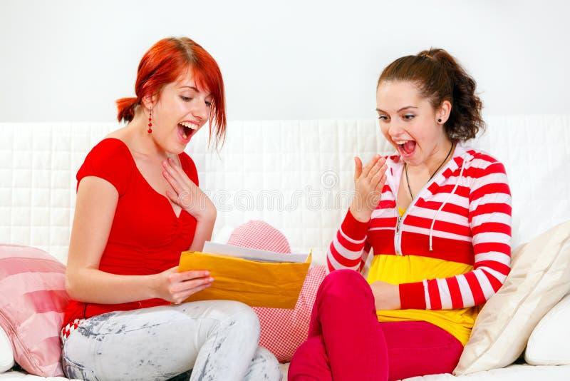 Amiche emozionanti che leggono lettera con le buone notizie fotografie stock