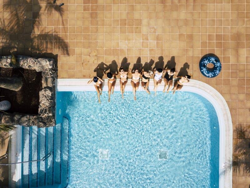 Amiche femmine caucasiche che si approfittano della piscina durante le vacanze estive in albergo o in località turistiche - vista fotografia stock libera da diritti