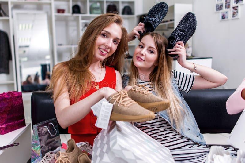 Amiche teenager positive divertendosi tempo insieme mentre facendo seduta di compera scegliendo le nuove scarpe che imbrogliano i immagini stock libere da diritti
