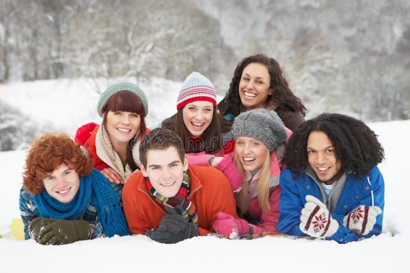 Amici adolescenti che hanno divertimento in neve fotografia stock