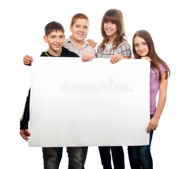 Amici adolescenti che tengono documento vuoto gigante fotografie stock libere da diritti